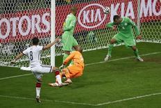 Jogador da Alemanha Mesut Ozil (esquerda) faz gol contra Argélia no Estádio do Beira-Rio, em Porto Alegre. 30/6/2014 REUTERS/Leonhard Foeger