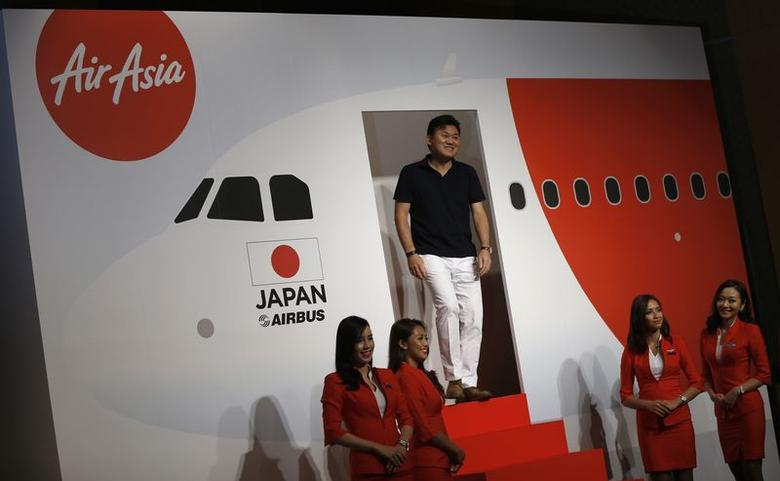 Chairman and CEO of e-commerce operator Rakuten Inc Hiroshi Mikitani (C) makes an appearance before the media during an AirAsia Group news conference in Tokyo July 1, 2014. REUTERS/Issei Kato