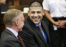 Former New England Patriots football player Aaron Hernandez (R) smiles while speaking with his defense attorney Charlie Rankin before a hearing in Suffolk Superior Court before a hearing in Boston, Massachusetts, June 24, 2014. REUTERS/Steven Senne/Pool