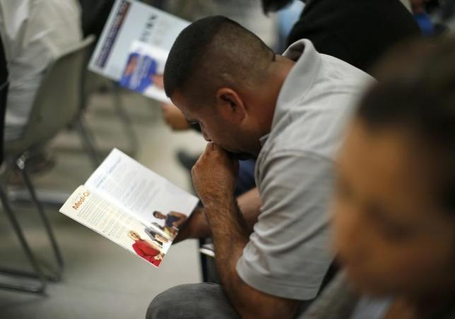 People read pamphlets as they wait in line at a health insurance enrollment event in Cudahy, California March 27, 2014.  REUTERS/Lucy Nicholson