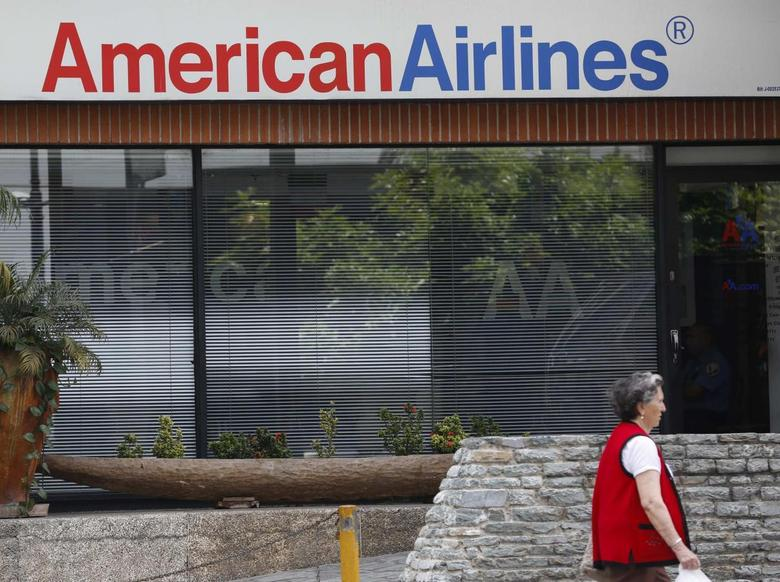 A woman walks past an American Airlines office in Caracas June 17, 2014.  REUTERS/Carlos Garcia Rawlins