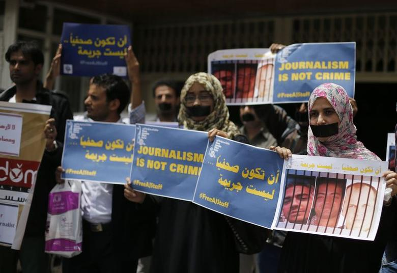 Journalists protest the imprisonment of Al Jazeera journalists Peter Greste, Mohamed Fahmy and Baher Mohamed in Egypt, by taping up their mouths outside Al Jazeera offices in Sanaa June 25, 2014. REUTERS/Khaled Abdullah