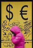 Пешеход проходит мимо пункта обмена валюты в Москве 3 марта 2014 года. Рубль восстанавливается в среду после существенного падения накануне из-за возобновления боевых действий на Украине и снижения продаж экспортной выручки в начале месяца. REUTERS/Maxim Shemetov