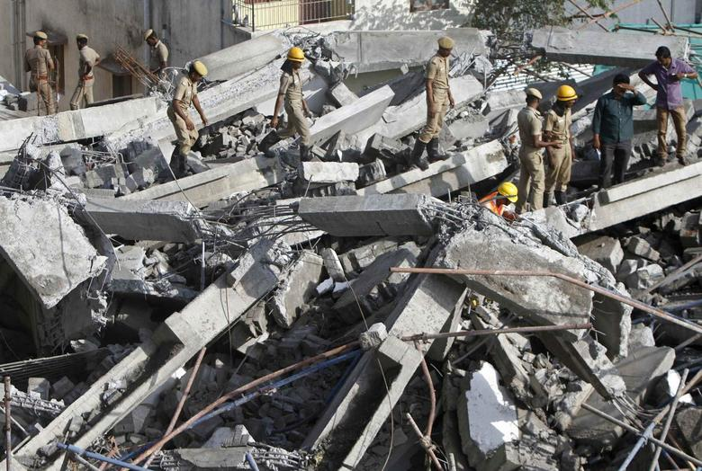 Rescue workers conduct a search operation for survivors at the site of a collapsed 11-storey building that was under construction on the outskirts of the southern Indian city of Chennai June 29, 2014. REUTERS/Babu