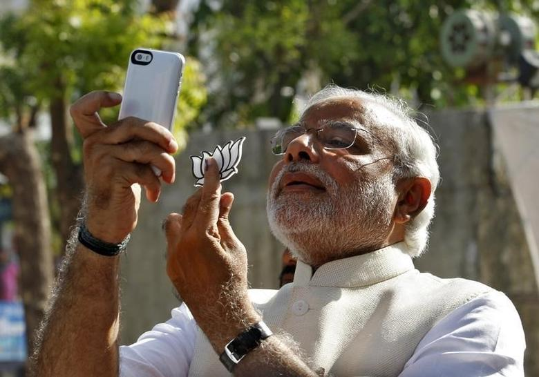 Hindu nationalist Narendra Modi, the prime ministerial candidate for India's main opposition Bharatiya Janata Party (BJP), takes a ''selfie'' with a mobile phone after casting his vote at a polling station during the seventh phase of India's general election in the western Indian city of Ahmedabad April 30, 2014.  REUTERS/Amit Dave