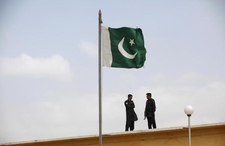 A Pakistani flag flies on a mast as paramilitary Frontier Corps soldiers talk while guarding at Karachi's District Malir prison, August 23, 2013.  REUTERS/Akhtar Soomro