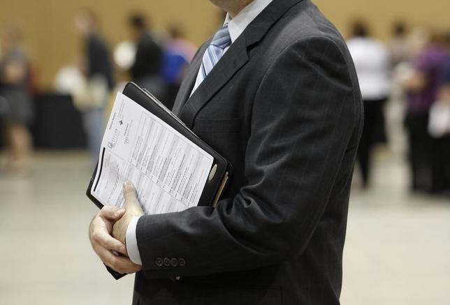 A job seeker holds his binder filled with resumes as he waits in line before speaking with a recruiter during a health care job fair in Phoenix, Arizona November 4, 2009. REUTERS/Joshua Lott