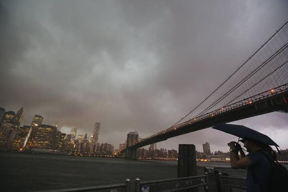A man stands underneath the Brooklyn Bridge to photograph a summer storm bearing down on New York July 2, 2014.  REUTERS/Lucas Jackson