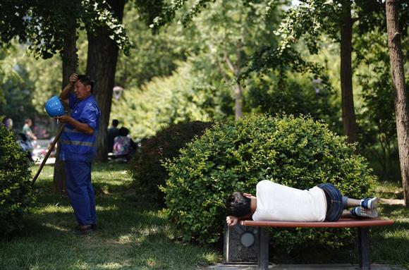 A worker wipes sweat on his forehead next a man taking a nap on a bench, in Beijing June 23, 2014.  REUTERS/Kim Kyung-Hoon