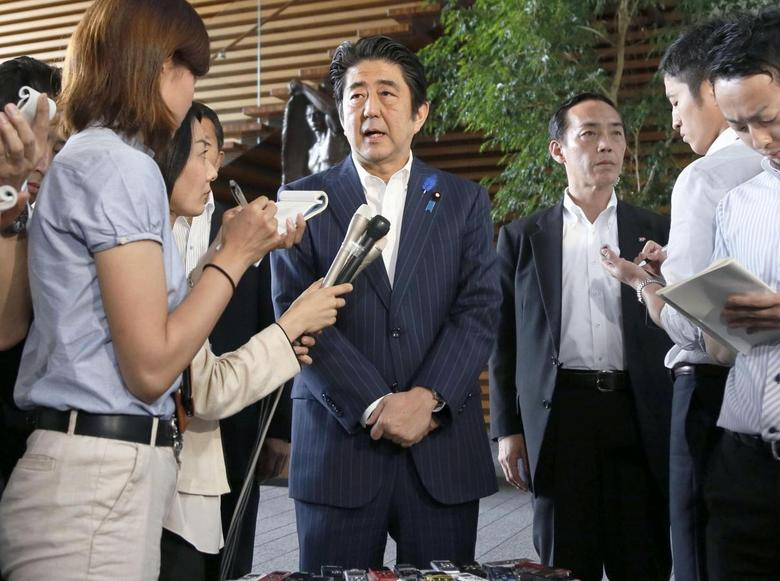 Japan's Prime Minister Shinzo Abe (C) speaks to media at his official residence in Tokyo July 3, 2014 in this photo taken by Kyodo.  REUTERS/Kyodo
