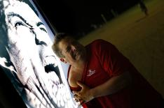 Un hombre posa junto a un afiche con el rostro de Luis Suárez en la playa de Copacabana en Río de Janeiro, jun 26 2014. ¿Cuál es la diferencia entre una bolsa de té y la selección de fútbol de Inglaterra?. ¡Que la bolsa de té dura más en una copa!    REUTERS/Kai Pfaffenbach