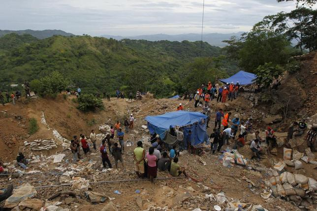 Residents and rescue workers stand at the site of a landslide at a gold mine in San Juan Arriba, on the outskirts of Tegucigalpa July 3, 2014.  REUTERS/Jorge Cabrera