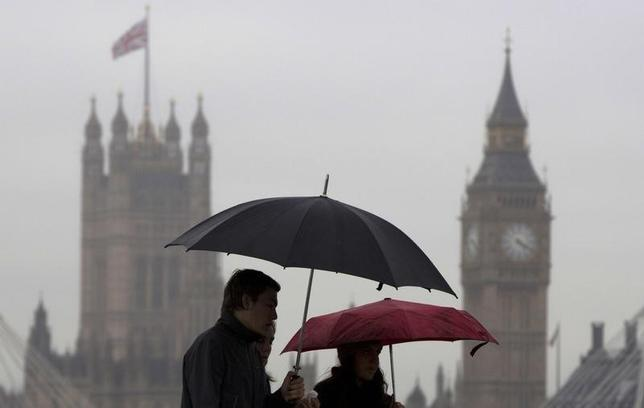 Pedestrians carry umbrellas on a rainy day in London May 27, 2014. REUTERS/Neil Hall