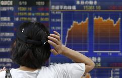 A woman scratching her head looks at an electronic board showing the graph of the recent fluctuations of Japan's Nikkei average outside a brokerage in Tokyo June 19, 2014. REUTERS/Yuya Shino