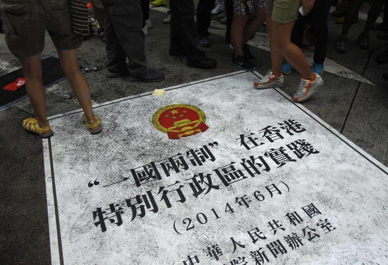 People step on a sign depicting an enlarged cover of China's recent ''One country, two systems'' white paper over the control of Hong Kong, during a mass protest demanding universal suffrage in Hong Kong July 1, 2014. REUTERS/Liau Chung-ren