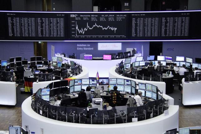 Traders are pictured at their desks in front of the DAX board at the Frankfurt stock exchange, July 1, 2014. REUTERS/Remote/Thomas Peter