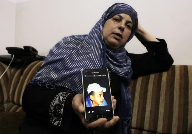 Suha, mother of Mohammed Abu Khudair, shows a picture of her son on her mobile phone at their home in Shuafat, an Arab suburb of Jerusalem July 2, 2014.  REUTERS/Ammar Awad