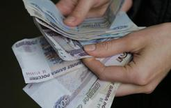 Торговец пересчитывает рублевые купюры на рынке в Москве 3 марта 2014 года. Рубль в минусе на малоликвидных пятничных торгах из-за желания минимизировать возможные риски к выходным; низкая торговая активность может сохраниться до конца биржевой сессии из-за закрытых американских рынков в День независимости США. REUTERS/Maxim Shemetov