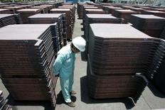 Un trabajor revisa una pila de cobre en PT Smelting en Gresike, en la provincia del este de Java, 19 de marzo de 2014. Los precios del cobre operaban cerca de su mayor nivel en más de cuatro meses el viernes y se encaminaban a anotar su mayor alza semanal en más de nueve meses debido a que datos de empleo alentadores en Estados Unidos aumentaron el panorama para la demanda de metales industriales. REUTERS/Sigit Pamungkas