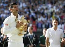 Sérvio Novak Djokovic segura taça após derrotar o suíço Roger Federer na final de Wimbledon, em Londres. 6/7/2014 REUTERS/Stefan Wermuth