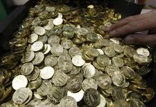 Десятирублевые монеты на монетном дворе в Санкт-Петербурге, 9 февраля 2010 года. Рубль слабеет утром понедельника к бивалютной корзине и её компонентам за счет локального спроса на валюту, на фоне дешевеющей нефти и дорожающего доллара США на мировых рынках. REUTERS/Alexander Demianchuk
