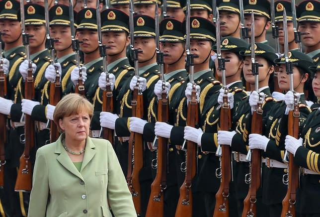 Germany's Chancellor Angela Merkel reviews an honour guard during a welcoming ceremony outside the Great Hall of the People in Beijing July 7, 2014.   REUTERS/Kim Kyung-Hoon   (CHINA - Tags: POLITICS)