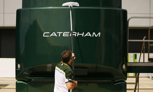 A member of the Caterham Formula One team cleans one of the team vehicles ahead of the British Grand Prix at the Silverstone race circuit, central England, July 3, 2014. REUTERS/Phil Noble