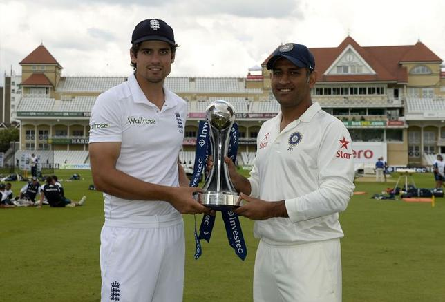 England's captain Alastair Cook (L) stands with India's captain Mahendra Singh Dhoni holding the series trophy before Wednesday's first test cricket match at Trent Bridge cricket ground in Nottingham, July 8, 2014. REUTERS/Philip Brown