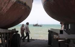 Люди и яхты на пляже в Евпатории, 6 апреля 2014 года. Молдавия запретила судам под своим флагом заходить в порты аннексированного Россией Крыма, на следующий день после того, как Украина пригрозила проблемами иностранным судовладельцам. REUTERS/Stringer