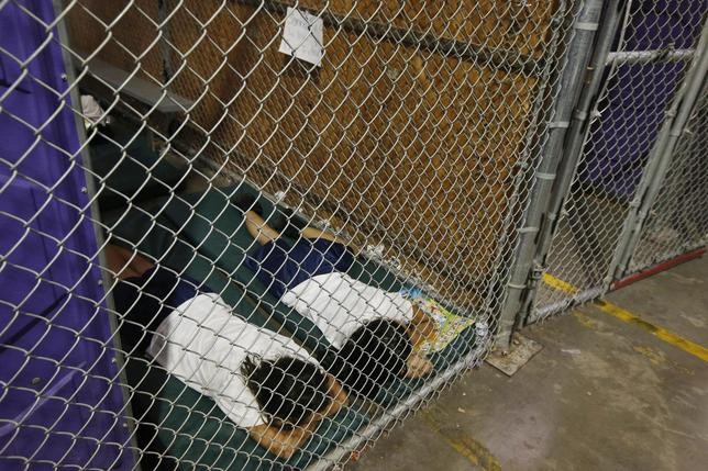 Two female detainees sleep in a holding cell, as the children are separated by age group and gender, as hundreds of mostly Central American immigrant children are being processed and held at the U.S. Customs and Border Protection (CBP) Nogales Placement Center in Nogales, Arizona, June 18, 2014.  REUTERS/Ross D. Franklin/Pool