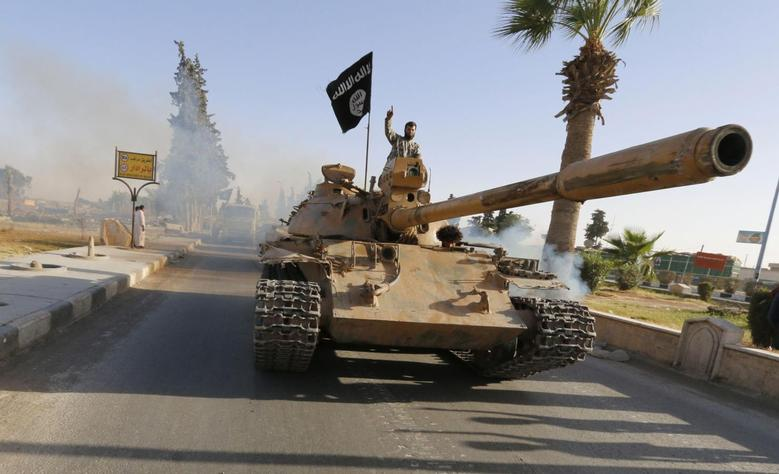 Militant Islamist fighters on a tank take part in a military parade along the streets of northern Raqqa province June 30, 2014.REUTERS/Stringer