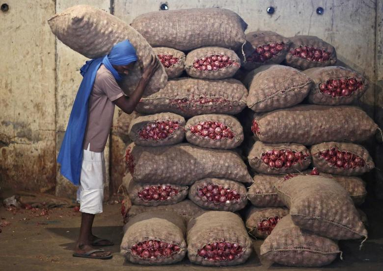 A labourer stacks a sack of onions in a storage room at a wholesale vegetable and fruit market in New Delhi July 2, 2014.  REUTERS/Anindito Mukherjee