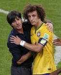 David Luiz é confortado pelo técnico alemão Loew em Belo Horizonte. 08/07/2014 REUTERS/David Gray