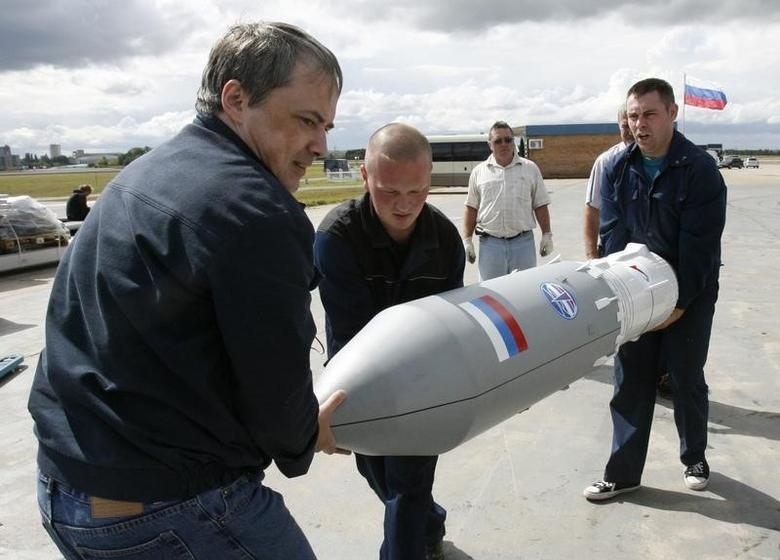 Workers carry a part of a Russian Angara rocket to put it on display as they prepare for the MAKS-2009 international air show in Zhukovsky, outside Moscow, August 14, 2009. REUTERS/Sergei Karpukhin/Files