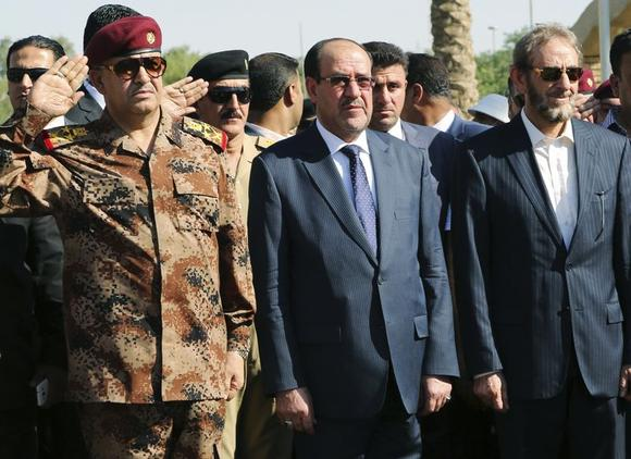 Iraq's Prime Minister Nuri al-Maliki (C) and acting Defence Minister Saadoun al-Dulaimi (R) attend the funeral ceremony of Major General Negm Abdullah Ali, commander of the army's sixth division, at the defence ministry in Baghdad July 7, 2014.  REUTERS/Stringer