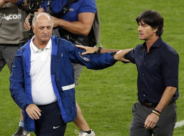 Brazil's coach Luiz Felipe Scolari (L) congratulates Germany's coach Joachim Loew after Germany won their 2014 World Cup semi-finals at the Mineirao stadium in Belo Horizonte July 8, 2014. REUTERS/David Gray
