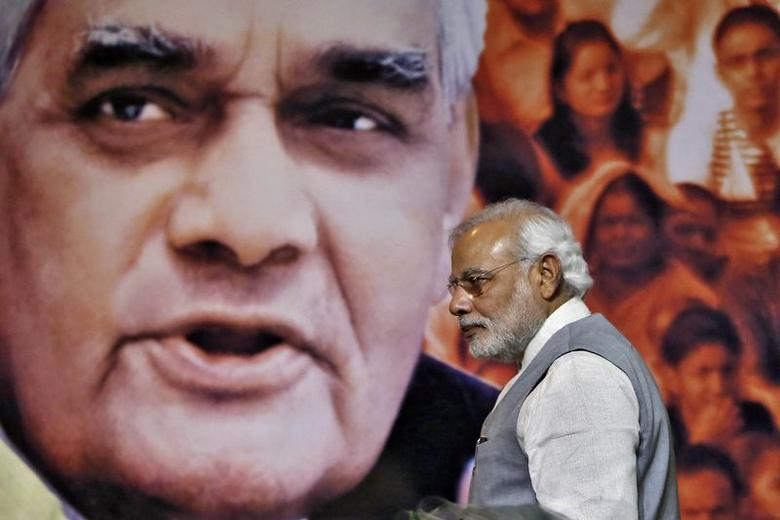 Prime Minister Narendra Modi walks in front of a picture of former Indian Prime Minister Atal Behari Vajpayee after a news conference in New Delhi July 9, 2014. REUTERS/Anindito Mukherjee