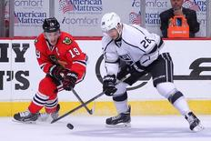 Chicago Blackhawks center Jonathan Toews (19) steals the puck from Los Angeles Kings defenseman Slava Voynov (26) during the second period in game seven of the Western Conference Final of the 2014 Stanley Cup Playoffs at the United Center. Jun 1, 2014; Chicago,USA;Dennis Wierzbicki-USA TODAY Sports