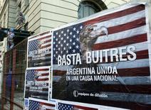 """Construction workers work near posters that read """"Enough vultures, Argentina united for a national cause"""" in Buenos Aires June 18, 2014.  REUTERS/Enrique Marcarian"""