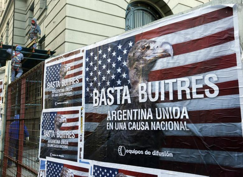 Construction workers work near posters that read ''Enough vultures, Argentina united for a national cause'' in Buenos Aires June 18, 2014.  REUTERS/Enrique Marcarian