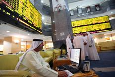 An investor monitors a screen displaying stock information at the Abu Dhabi Securities Exchange June 25, 2014.   REUTERS/Stringer