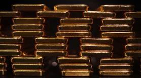Золотые слитки в хранилище  ProAurum в Мюнхене 6 марта 2014 года. Цены на золото растут за счет ослабления доллара после публикации протокола последнего совещания ФРС, из которого не стало понятно, когда центробанк планирует повышать процентные ставки. REUTERS/Michael Dalder