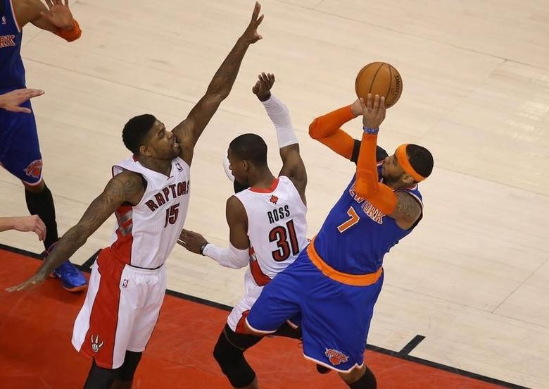 New York Knicks forward Carmelo Anthony (7) shoots against Toronto Raptors forward Amir Johnson (15) at Air Canada Centre. Apr 11, 2014; Toronto, Ontario, CANADA; Tom Szczerbowski-USA TODAY Sports