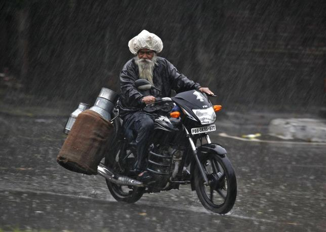 A milkman rides a motorcycle during a heavy rain shower in Chandigarh July 2, 2014.  REUTERS/Ajay Verma
