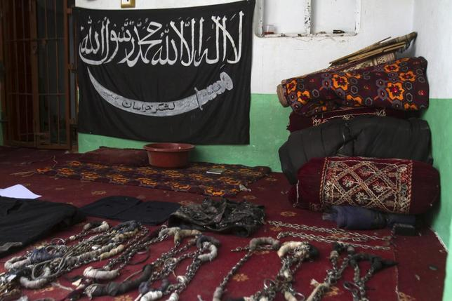 A black Jihad flag, handcuffs and chains are displayed in a house used by Taliban militants as a prison after a military operation against the militants in the town of Miranshah in North Waziristan July 9, 2014. REUTERS/Maqsood Mehdi