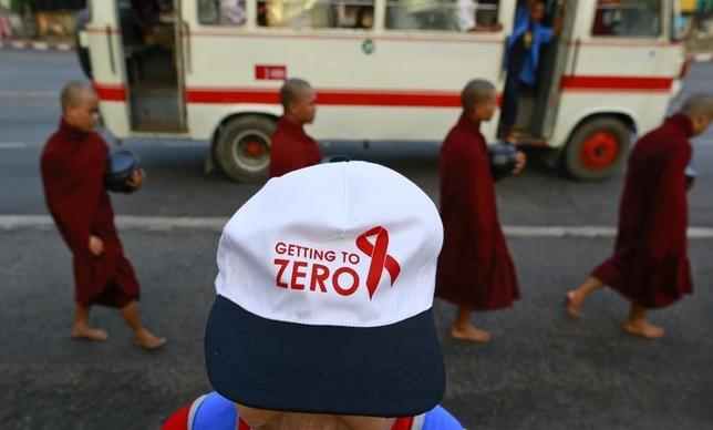 A logo is seen on the cap of a woman standing near Buddhist monks walking on a road to collect alums, during a march ahead of World AIDS Day 2013 at Kandawgyi garden in Yangon November 30, 2013. REUTERS/Soe Zeya Tun/Files