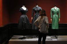 "A visitor looks at vintage dresses by designers Christian Dior, Jacques Heim and Givenchy presented in the exhibition ""Les Annees 50, La mode en France"" (The 50s. Fashion in France, 1947-1957) at the Palais Galliera  fashion museum in Paris, July 10, 2014. REUTERS/Benoit Tessier"
