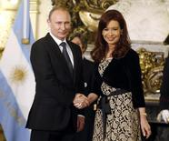 Argentina's President Cristina Fernandez de Kirchner (R) shakes hands with her Russian counterpart Vladimir Putin at the Casa Rosada presidential palace in Buenos Aires July 12, 2014.   REUTERS/Enrique Marcarian