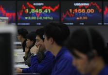 Валютные дилеры Korea Exchange Bank (KEB) в Сеуле 22 декабря 2011 года. Азиатские фондовые рынки выросли в понедельник за счет отдельных отраслей. REUTERS/Kim Hong-Ji
