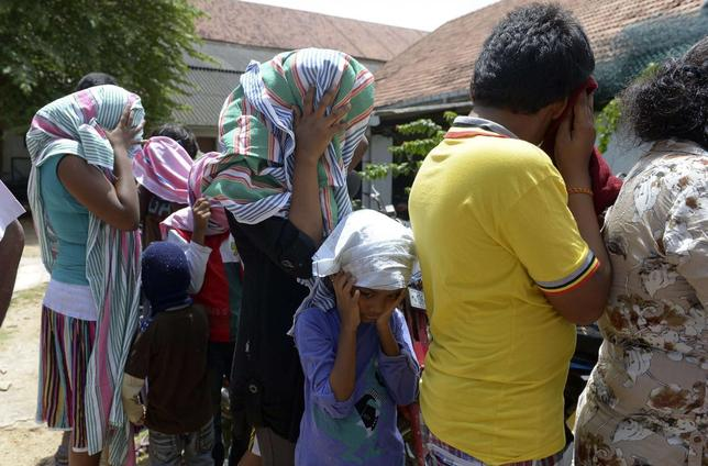 Sri Lankan asylum seekers who were sent back by Australia cover their faces as they wait to enter a magistrate's court in the southern port district of Galle July 8, 2014.  REUTERS/Stringer